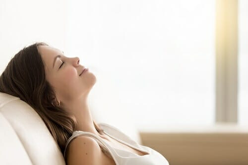 Woman sitting with eyes closed smiling