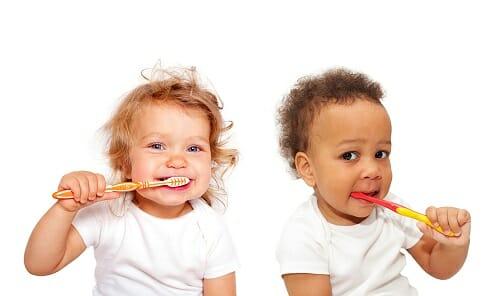 Two babies brushing teeth